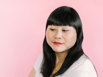 A picture of a woman with black hair against a pink background