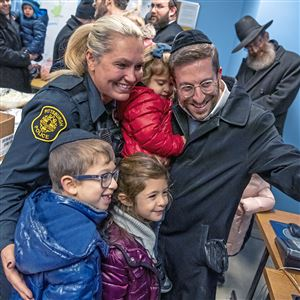 Pittsburgh police Officer Victoria Butch, left, takes a selfie with Yossi Berkowitz and his children, from left, Zevi, Devora, and Kayla, of Squirrel Hill, after they delivered Thanksgiving food and thank you cards to the Zone 4 station in Squirrel Hill on Thanksgiving Day.