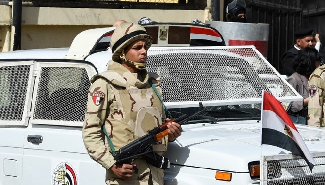 A picture taken on March 26, 2018 shows an Egyptian army conscript standing guard outside a polling station in the capital Cairo on the first day of the 2018 presidential elections. - Egyptians head to the polls in a three-day vote to choose between incumbent Abdel Fattah al-Sisi and little-known candidate Moussa Mostafa Moussa, who has struggled to make the case he is not Sisi's minion. (Photo by FETHI BELAID / AFP)