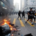 "Anti-government protesters set fire to block traffic and run as police arrive in Hong Kong, Tuesday, Oct. 1, 2019. Thousands of black-clad protesters marched in central Hong Kong as part of multiple pro-democracy rallies Tuesday urging China's Communist Party to ""return power to the people"" as the party celebrated its 70th year of rule. (AP Photo/Gemunu Amarasinghe )"