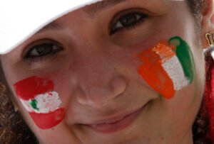 A member of Lebanese community in Ivory Coast smiles with her face painted with Ivory Coast and Lebanon flags colours at the Felix Houphouet Boigny international airport in Abidjan on March 14