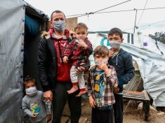 A migrant family wearing handmade protective face masks stand next to their tent in the camp of Moria in the island of Lesbos on March 28, 2020 as as the country is under lockdown to stop the spread of Covid-19 disease caused by the novel coronavirus. (Photo by Manolis LAGOUTARIS / AFP) (Photo by MANOLIS LAGOUTARIS/AFP via Getty Images)