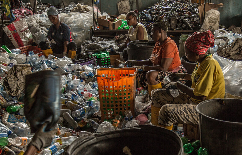 Waste collection and recycling - workers cleaning waste bottles for recycling purposes
