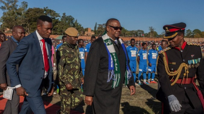Malawi President Arthur Peter Mutharika (C) wears two football club scarves of the teams of a friendly match as part of national celebrations to commemorate the country's 54th Independence Anniversary, July 6, 2018. (Photo by Amos Gumulira / AFP)