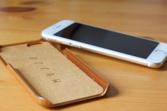 Mujjo Leather Case in Tan with an iPhone 6 propped up against it