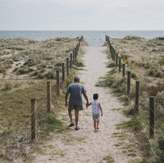 man and boy walking across pathway heading to beach
