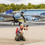Michael Raymond photographing P-51 Mustangs with WWII U.S. Navy fighters in the background.
