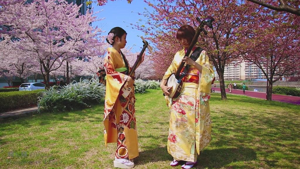 Two Japanese women playing shamisens.