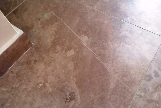 Scratched travertine tiled floor before cleaning in Hunt