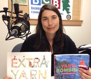 "Carmine Rau, Youth Services Librarian at Bainbridge Public Library, holds up two books that prove that she did not make up the idea of ""yarn bombing"""