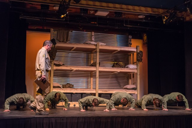 Photo by SG Atkinson: Sgt. Merwin J. Toomey (John Haas) closely inspects the rag-tag group of boys that he must turn into soldiers as they work on their push-ups during a recent rehearsal of Biloxi Blues.