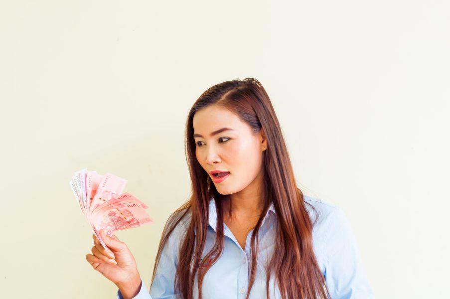 Тайская девушка смотрит на деньги
