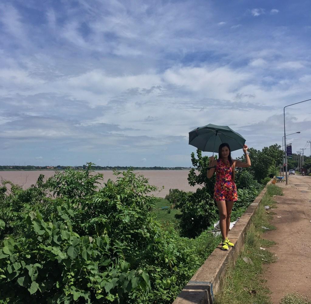 Жена на набережной, на фоне реки Меконг и тайского города Мукдахан