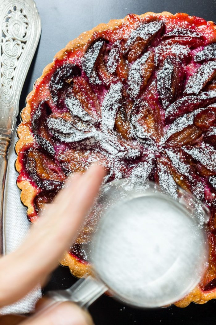 Dusting the finished Zwetschkenkuchen (plum tart) with confectioner's sugar.