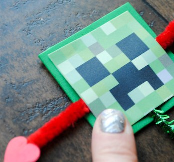 Step 7: Glue the four corners of the minecraft creeper face onto green foam square covering arrow middle