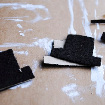 Step 3: Cut out hat shapes from the black felt. Layer 2 pieces of felt for each hat so they are the same shape.