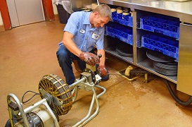 United Plumbing - Emergency-Services-Emergency-Plumber-Springfield-Missouri- image of repairman working on a drain in a commercial kitchen