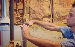 United Plumbing - Water-Heaters-–-Top-Plumbing-Springfield-Missouri-image of repairman working on a water heater