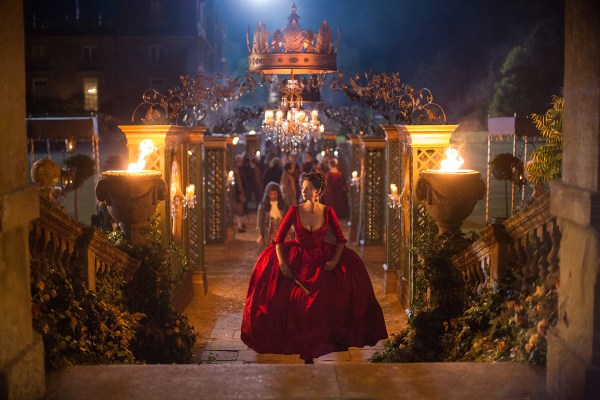 Claire walking into the court gardens in a large red dress.