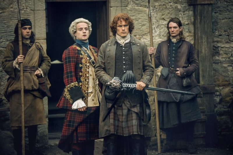 Guard 1: Dude, is he rubbing Fraser's back? Guard 2: Idk, just...just stand there and guard stuff. (Center right, Sam Heughan as Jamie Fraser.)