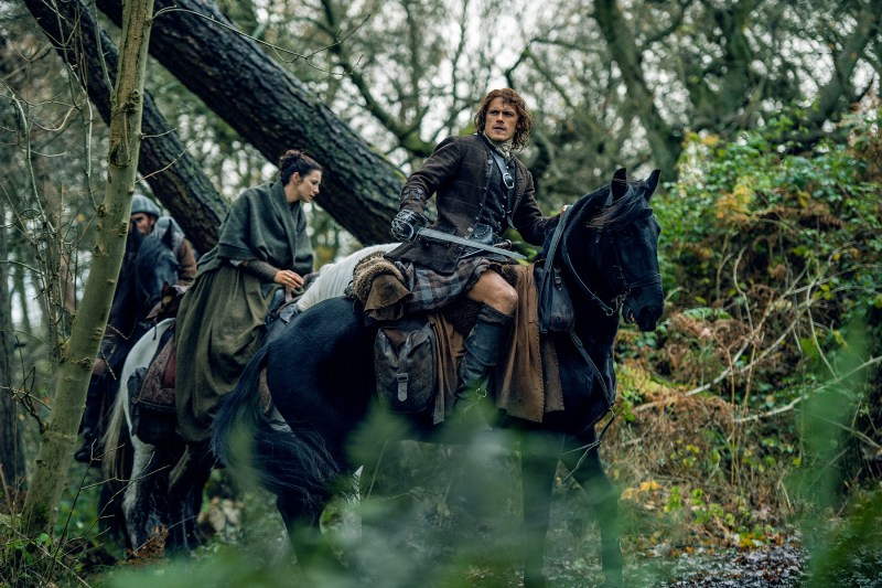 Of course, they look completely fabulous while doing it. (Left, Caitriona Balfe as Claire Fraser. Right, Sam Heughan as Jamie Fraser. They are riding horses through the woods.)