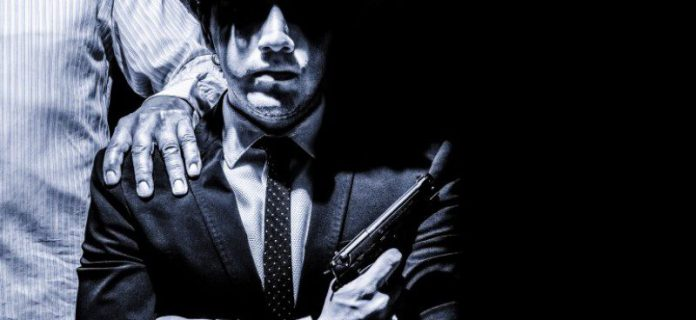mafia-man-young-gun-holding-pressure-godfather-suit-tie-shirt-sitting-hand-on-shoulder-dark-face-800