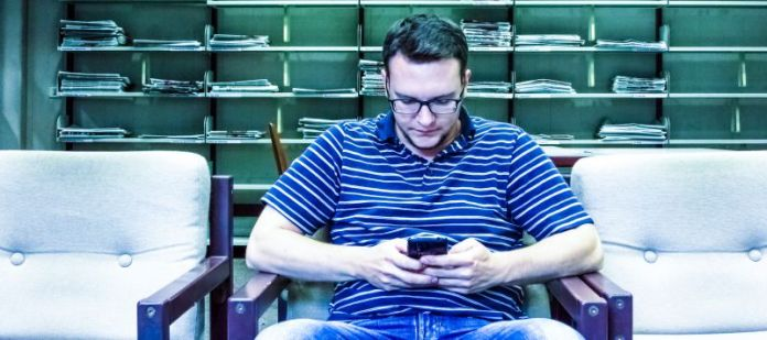 Man reading news on smartphone offline apps no data Sitting Chair inside Library