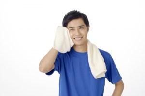 運動して顔の汗拭く男