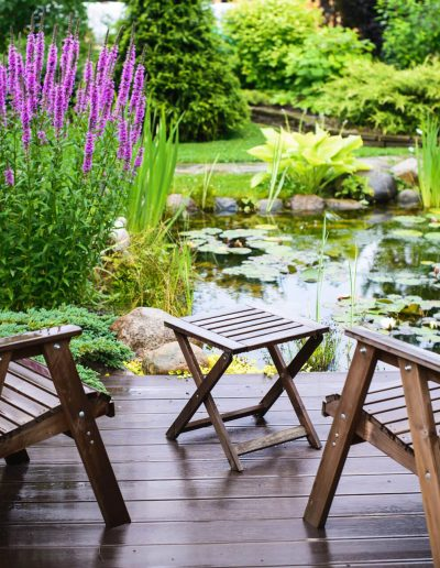 Two chairs on a deck on a garden pond