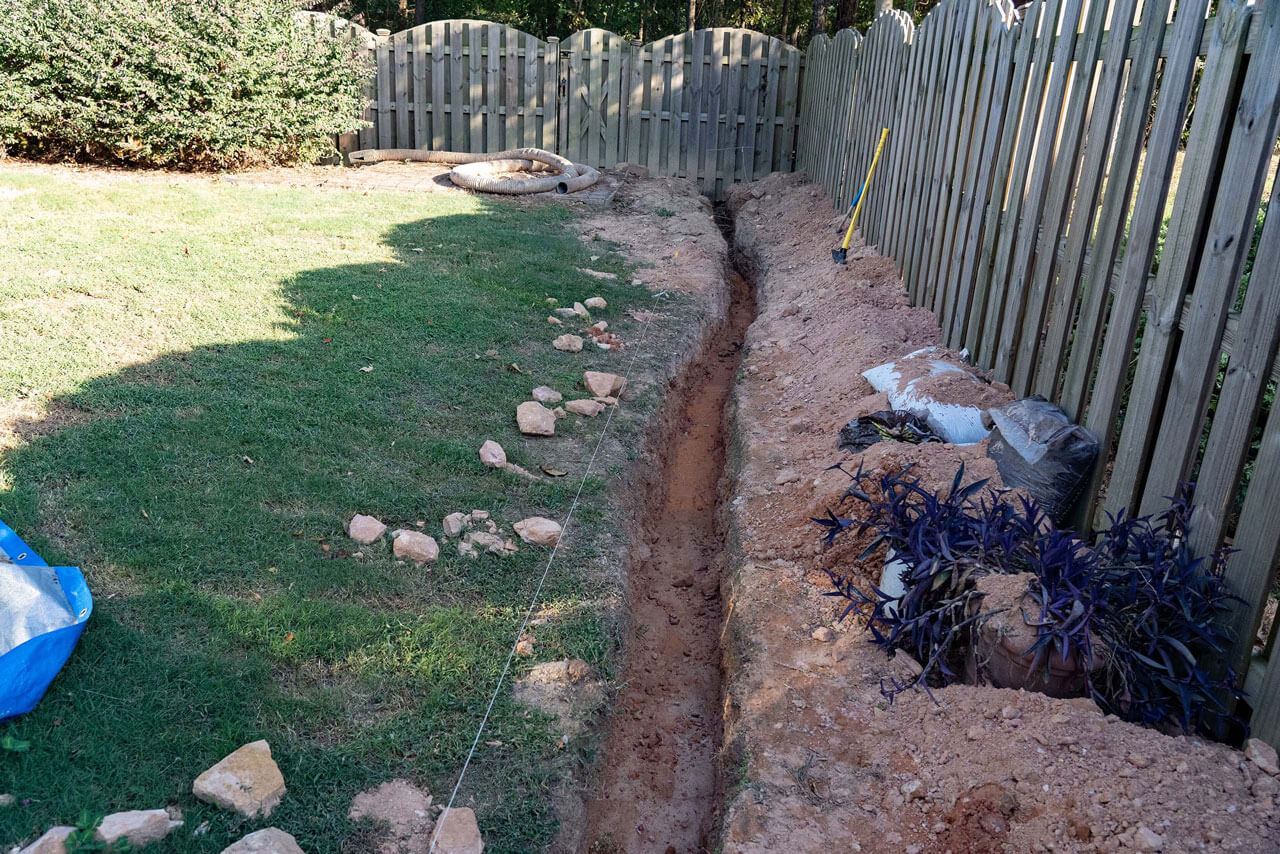 A trench is dug as the first step of a DIY French drain home imp