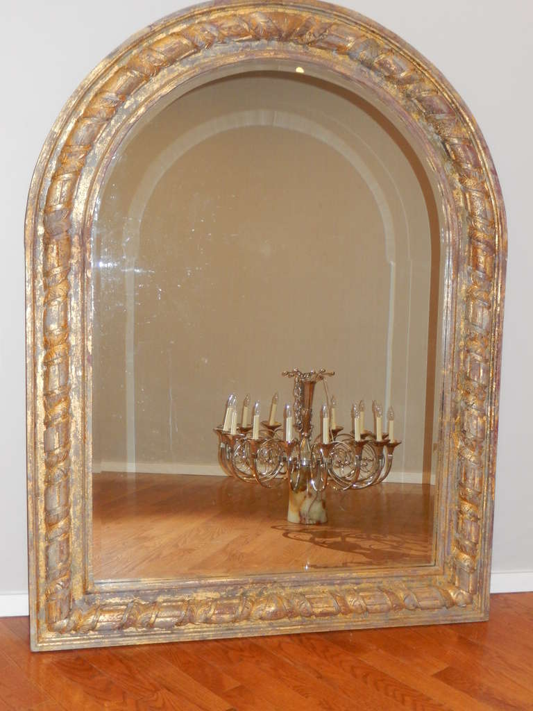 An Oversized French Arched Giltwood Carved Floor Mirror at