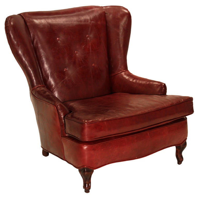 Obtuse oxblood leather and Walnut wing back chair For Sale