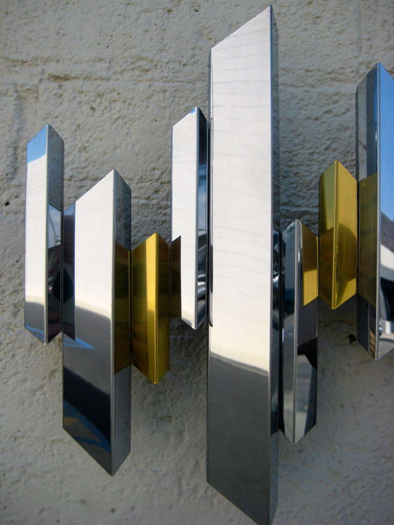 A sparkling chrome and brass cityscape wall sculpture by C