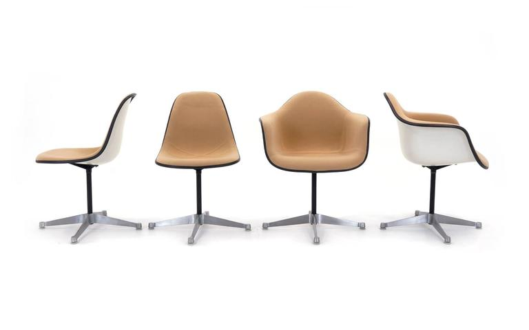 eames leather chair dining folding rocker lawn chairs set of eight upholstered swivel two arm and six charles ray fiberglass with cream colored upholstery