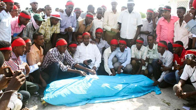 PHOTO: Fellow journalists and supporters crowd around the body of Ahmed Addow Anshur, who was murdered in the Somali capital of Mogadishu Wednesday.