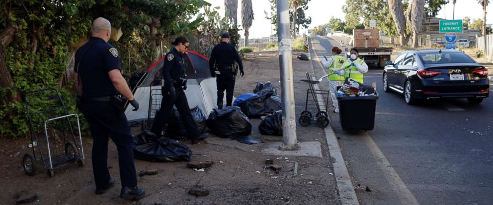 PHOTO: Police officers remove a tent left by the homeless during efforts to sanitize neighborhoods to control the spread of hepatitis A, in San Diego, Sept. 25, 2017.
