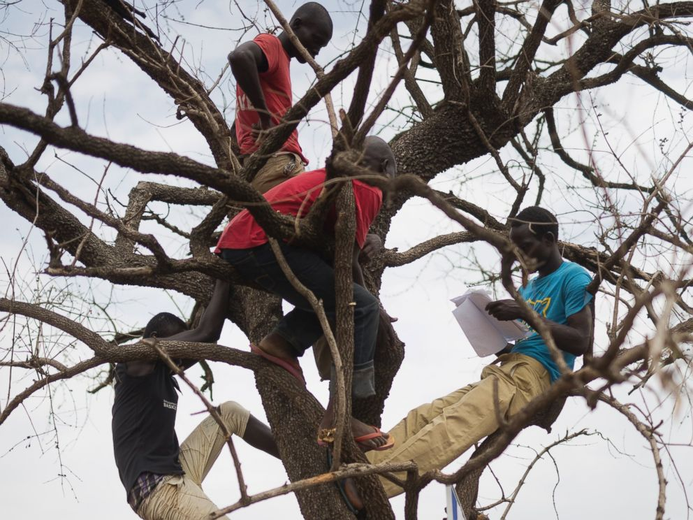 PHOTO: In this Monday, April 3, 2017 photo in the Imvepi camp, South Sudanese refugees gather under a tree from which names are announced for those allocated a land parcel from the Ugandan government.