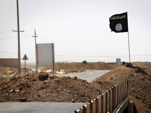 PHOTO: A flag of the Islamic State is seen on the other side of a bridge at the front line of fighting between Kurdish Peshmerga fighters and Islamist militants in Rashad, on the road between Kirkuk and Tikrit, Sept. 11, 2014.
