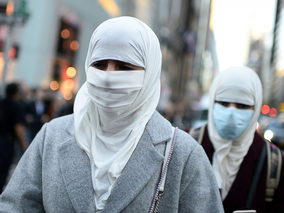 PHOTO: Two women wearing muslim head scarves walk along 57th Street and Fifth Avenue past anti-Trump protestors in New York City, Nov. 13, 2016.