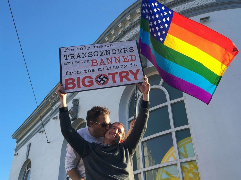 Nick Rondoletto, left, and Doug Thorogood, a couple from San Francisco, wave a rainbow flag and hold a sign against a proposed ban of transgendered people in the military at a protest in the Castro District. AP photo