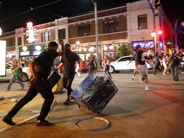 PHOTO: People overturn trash cans and throw objects as police try to clear a violent crowd Saturday, Sept. 16, 2017, in University City, Mo.