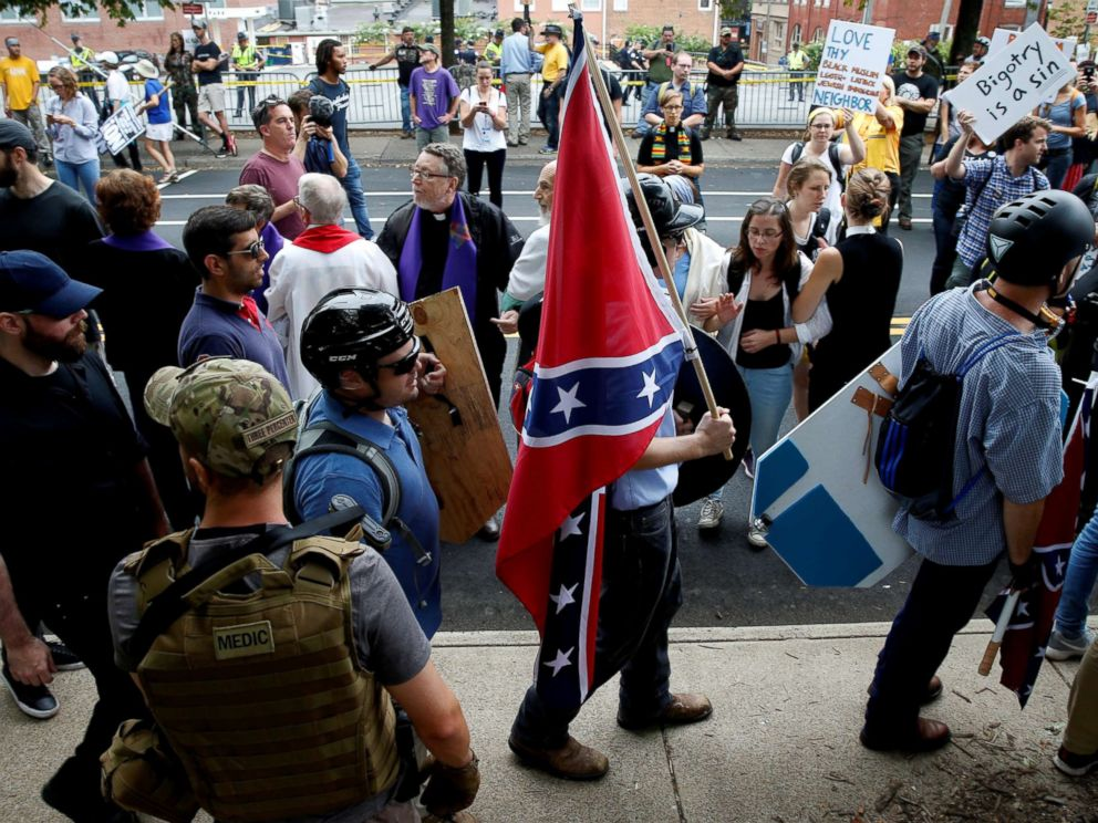PHOTO: A white supremacist carries the Confederate flag as he walks past counter demonstrators in Charlottesville, Va., Aug. 12, 2017.