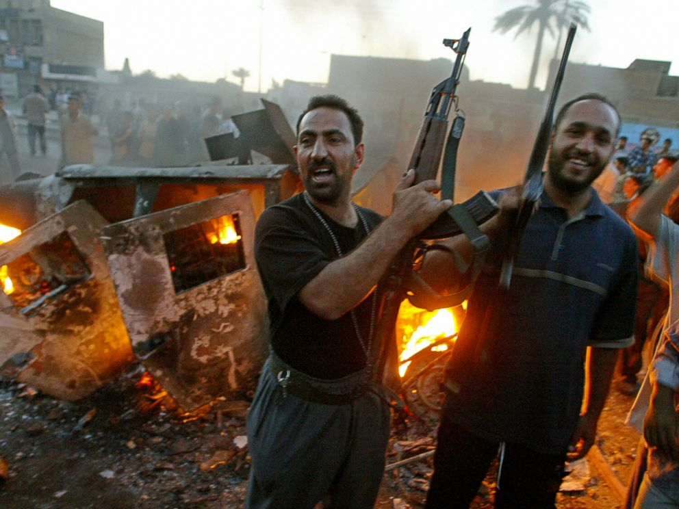 PHOTO: Armed Iraqi Muslim Shiites, member of Shiite radical leader Moqtada al-Sadr Army of Mehdi militia jubilate near a burning US Army Humvee during clashes in Baghdads al-Sadr City district, April 4, 2004.