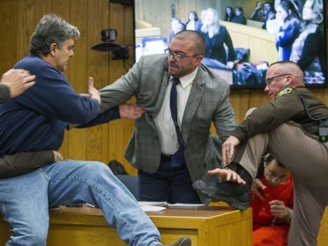 PHOTO: Randall Margraves, father of three victims of Larry Nassar, left, lunges at Nassar, bottom right, Feb. 2, 2018, in Eaton County Circuit Court in Charlotte, Mich.