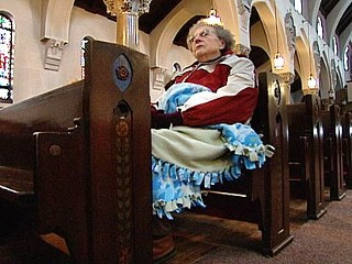 PHOTO A parishioner participates in a vigil being held to keep her church from being closed.