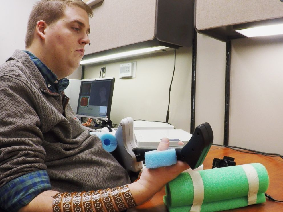 PHOTO: Ian Burkhart, 24, plays a guitar video game as part of a study into neural bypass technology that allowed him to regain functional use of his paralyzed hand.