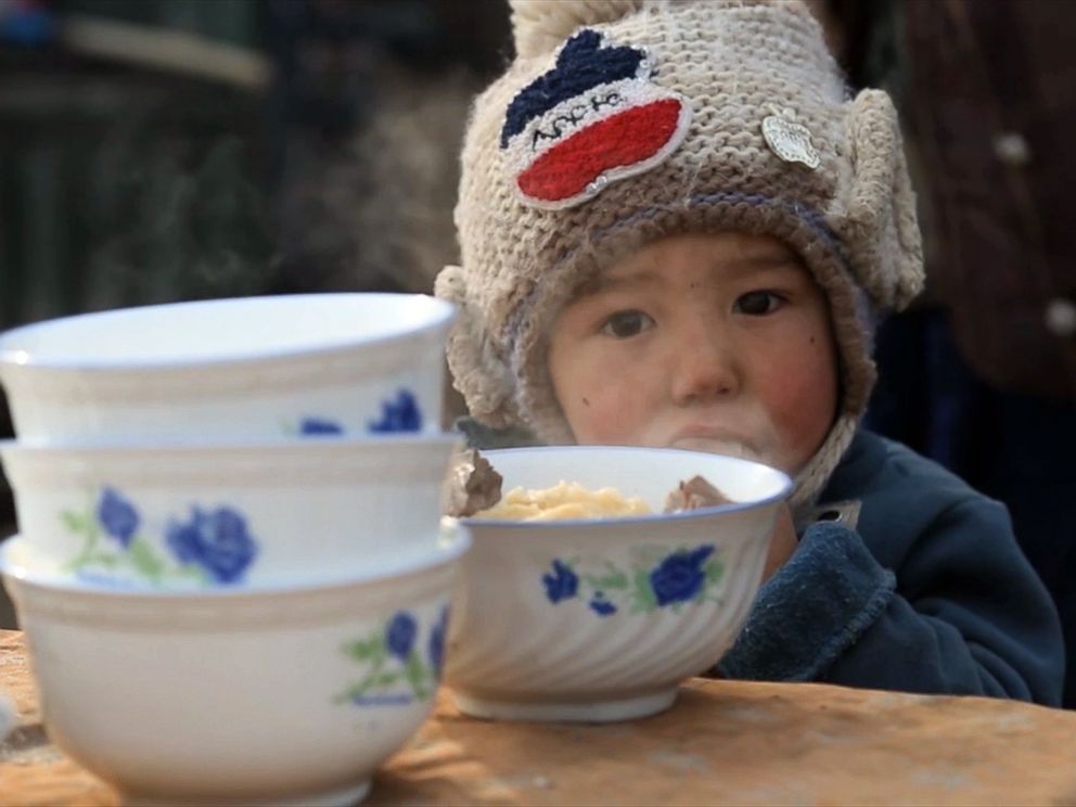 PHOTO: A young child eats lunch inside a Kashgar marketplace in Xinjiang, China in December 2015.