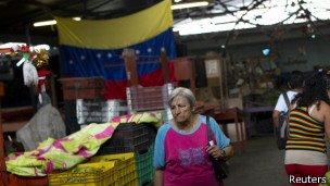 Una mujer camina en un mercado en Venezuela.