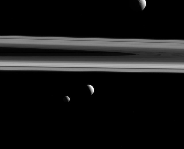 Three of Saturn's moons — Tethys, Enceladus, and Mimas — are captured in this group photo from NASA's Cassini spacecraft. Tethys (660 miles across) appears above the rings, while Enceladus (313 miles across) sits just below center. Mimas (246 miles across) hangs below and to the left of Enceladus. The image was taken in visible light with the Cassini spacecraft narrow-angle camera on Dec. 3, 2015. The view was acquired at a distance of approximately 837,000 miles from Enceladus.