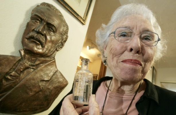 Catherine Mulholland with a portrait of grandfather William Mulholland and a bottle of Los Angeles Aqueduct water.